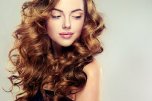 Young, brown haired woman with voluminous, shiny and wavy hair.
