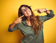 Young beautiful woman wearing green shirt and glasses over yelllow isolated background smiling cheerful showing and pointing with fingers teeth and mouth. Dental health concept.