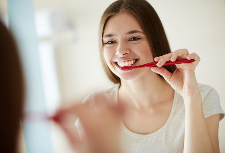 Young woman brushing teeth in mirror