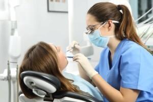 Woman patient having teeth cleaned by dental hygienist