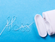 A string of floss that spells floss in cursive lays on the table as Ingenious Dentistry explains proper flossing frequency and practice